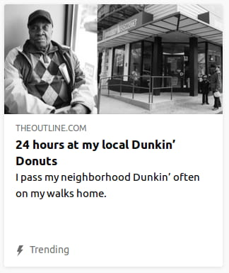 "By The Outline. Grayscale photo o' a guy in diamond-checkered sweater standing gainst a wall with a donut shop 'hind said wall. ""I pass my neighborhood Dunkin' often on my walks home."""