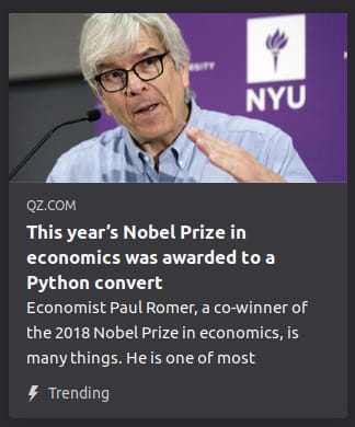 "By QZ. Photo o' an ol' man in front o' a microphone. ""Economist Paul Romer, a co-winner of the 2018 Nobel Prize in economics, is many things. He is one of most"""